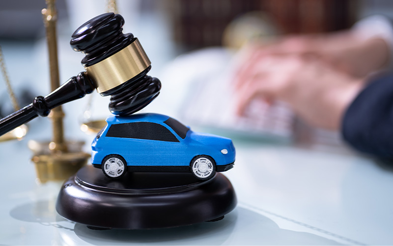Tiny model car with gavel resting on it.