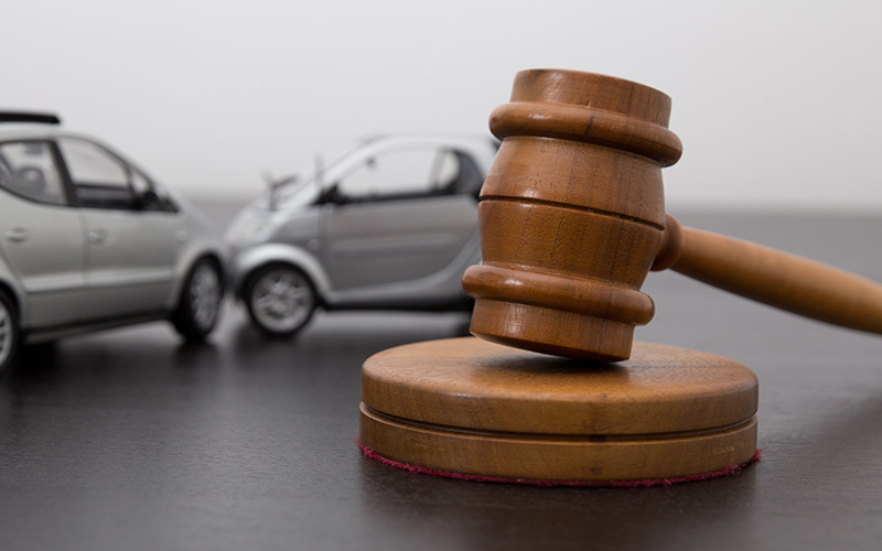 Gavel in foreground with two miniature cars colliding in the background.