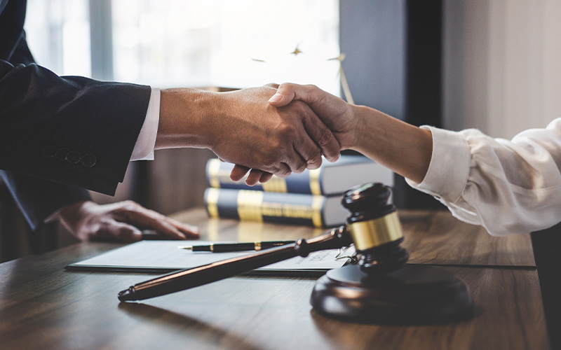 Lawyer and client shake hands with gavel in background