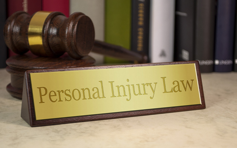 Golden sign with the words 'personal injury law' on a table with law books and gavel.